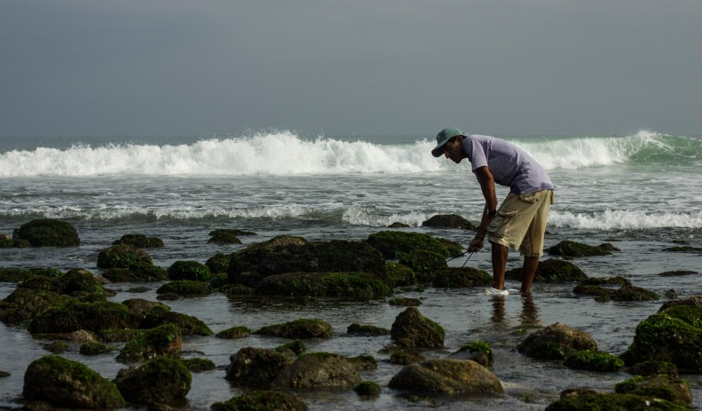 Mancora Guy looking in Rocks